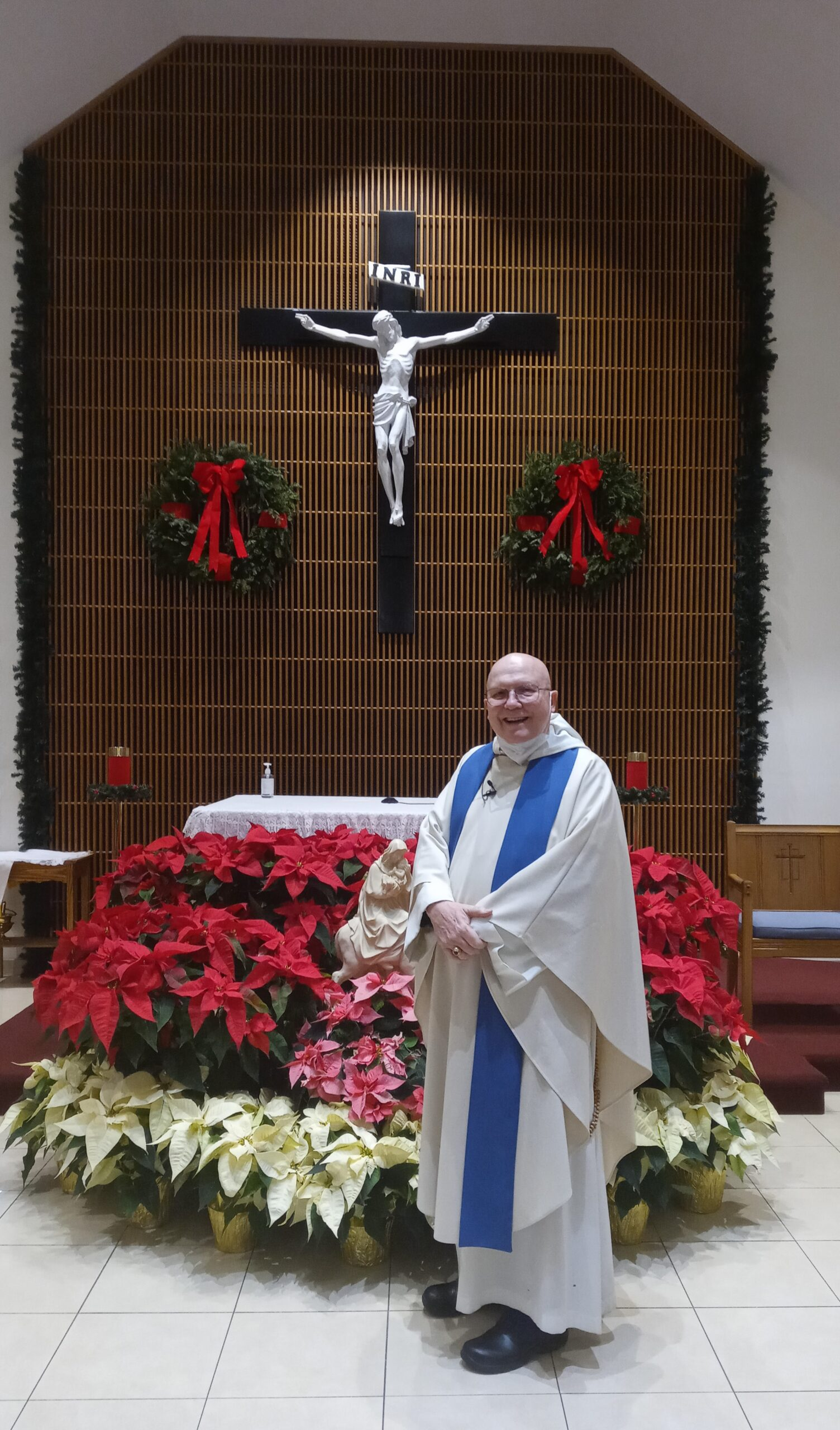 Father Hugh in front of Christmas Decorations